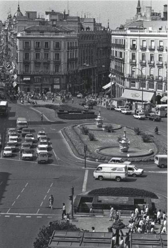 En 1984, Puerta del Sol est avant tout un espace circulatoire, offert au mouvement des automobiles, que l'architecte Manuel Herrero a réaménagé sobrement autour de deux fontaines et dans lequel le piéton ne peut pas se fixer durablement. (Source : Bernardo Perez Publié dans El País 19 mai 2013)