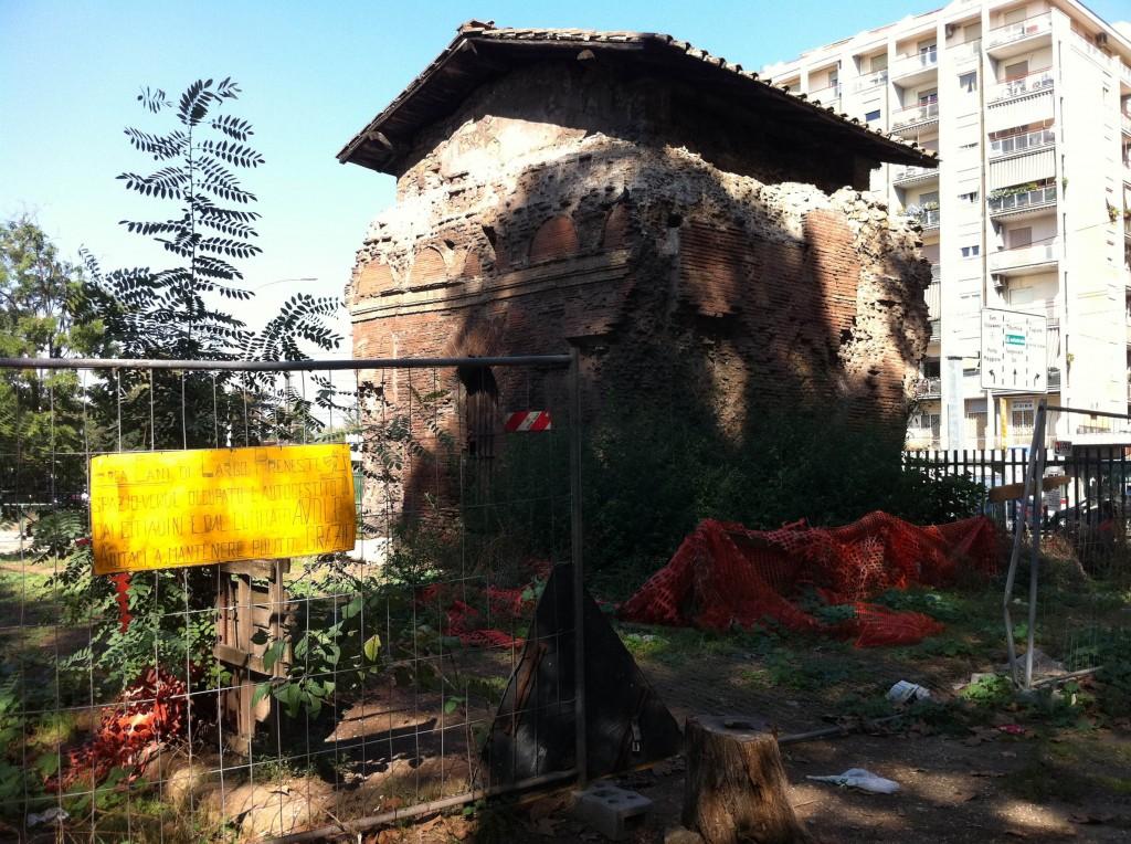 Colombarium romain du II-IIIe siècle après J.-C. abandonné, dans le Largo Preneste (quartier de Torpignattara). Certains habitants l'ont transformé en espace pour les chiens en cassant les barrières qui l'entourent. Sur le panneau jaune est écrit « Espace pour les chiens, zone verte occupée et auto-organisée par les citoyens. Aidez-nous à la maintenir propre. » (septembre 2013, source Cervelli)