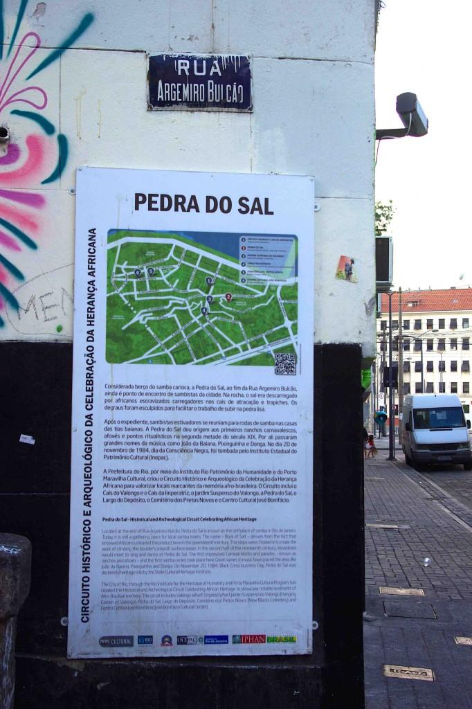 Au pied de la Pedra do Sal, rue Argemiro Bulcão, un panneau d'information touristique, des graffitis et une caméra de surveillance (L. Jouve-Villard, juillet 2013)