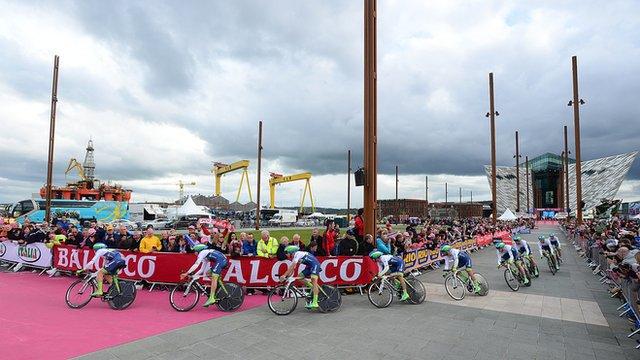 Lancement de la course Giro d'Italia en mai dernier: départ du Titanic Quarter. À l'arrière plan, le musée du Titanic dont la structure architecturale rappelle la proue d'un bateau. (BBC News Northern Ireland, 2014).