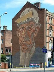 Fresque du centre-ville, commanditée par le conseil de la New Urban Left en 1984 et représentant le visage d'un sidérurgiste (Max Rousseau, 2006)