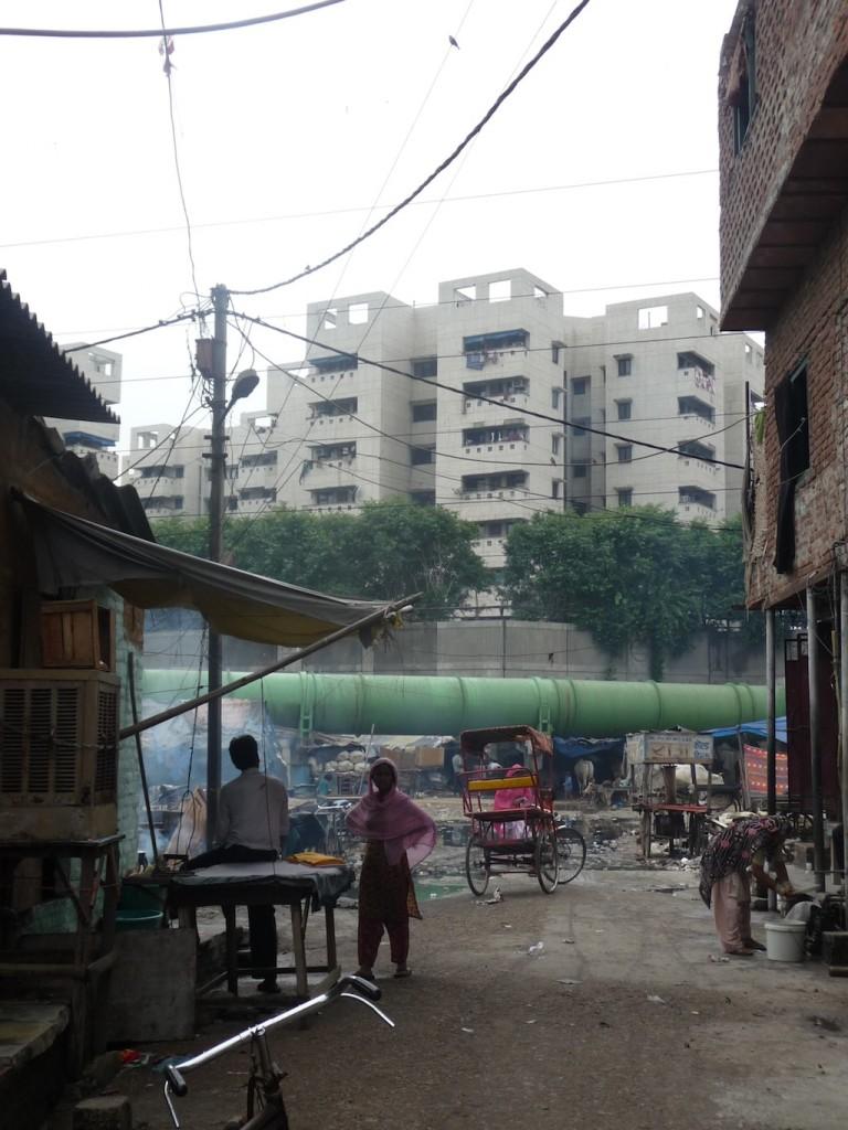 Le projet Shastri Park vu depuis les espaces résidentiels voisins. Les huttes accolées au mur du grand projet sont celles des anciens agriculteurs qui travaillaient la terre à l'endroit où le projet a été construit (Bon, 2012)