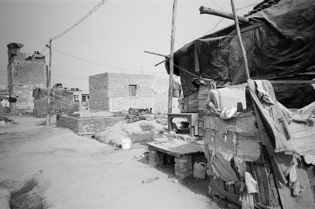 Illustration 2. Le lotissement de réinstallation de Narela, au nord-ouest de Delhi (Véronique Dupont, décembre 2000). Sept mois après la relocalisation, certaines familles n'ont pu réinstaller qu'un habitat très précaire, tandis que d'autres ont pu construire une maison en briques.