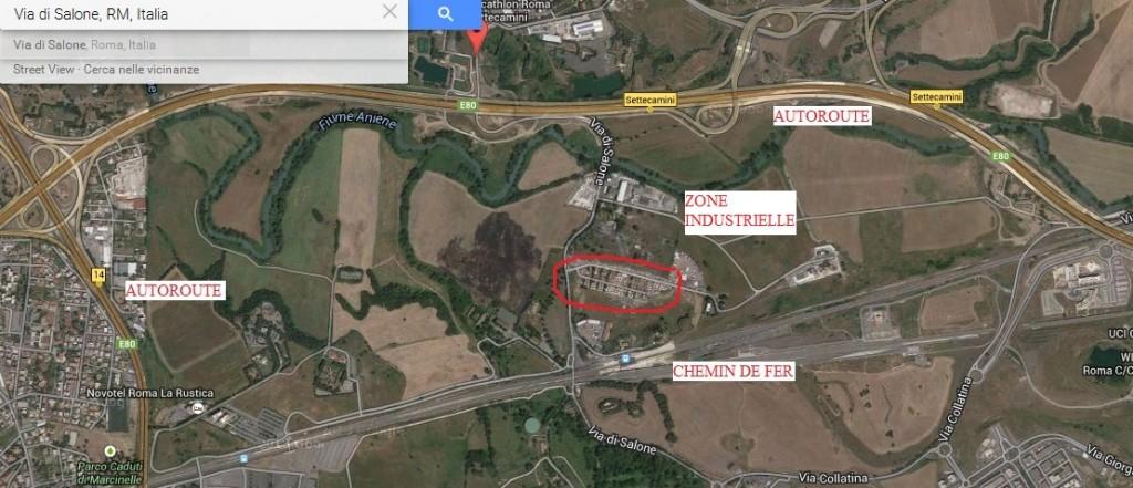 Vue aérienne. Le camp rom, entouré en rouge, se trouve au milieu de terrains vagues et agricoles et d'une zone industrielle. Il se situe entre l'autoroute et le chemin de fer. (Google maps, 2015)