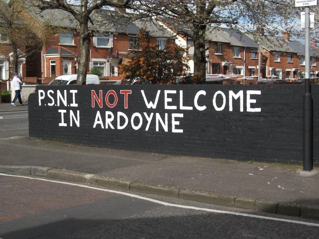 « PSNI [la police] n'est pas la bienvenue dans [le quartier d'] Ardoyne ». Cette inscription est une partie d'une peinture murale du Republican Network for Unity (RNU), organisation souvent décrite comme étant proche d'Óglaigh na hÉireann (groupe paramilitaire républicain qui s'oppose au processus de paix et qui reste impliqué dans des actions violentes contre les forces de sécurité britanniques). Elle illustre bien l'hostilité d'une certaine frange de la population nationaliste/catholique envers le service de police nord-irlandais. (Ardoyne – Belfast, Marotte, mars 2014)