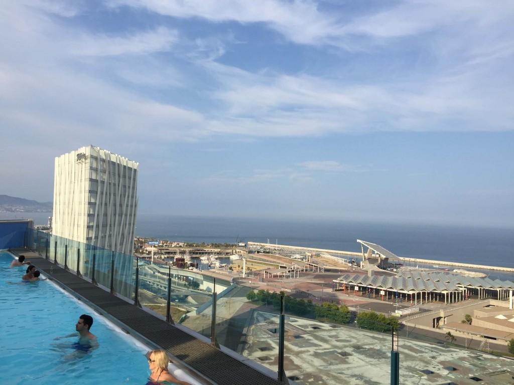2. Vue depuis la piscine de l'hôtel Barcelona Princess. On observe le toit du forum triangulaire d'Herzog & de Meuron au premier plan, la marina à gauche, les installations solaires à droite avec le panneau monumental d'où part la passerelle en fond. (Bouton, 2015)