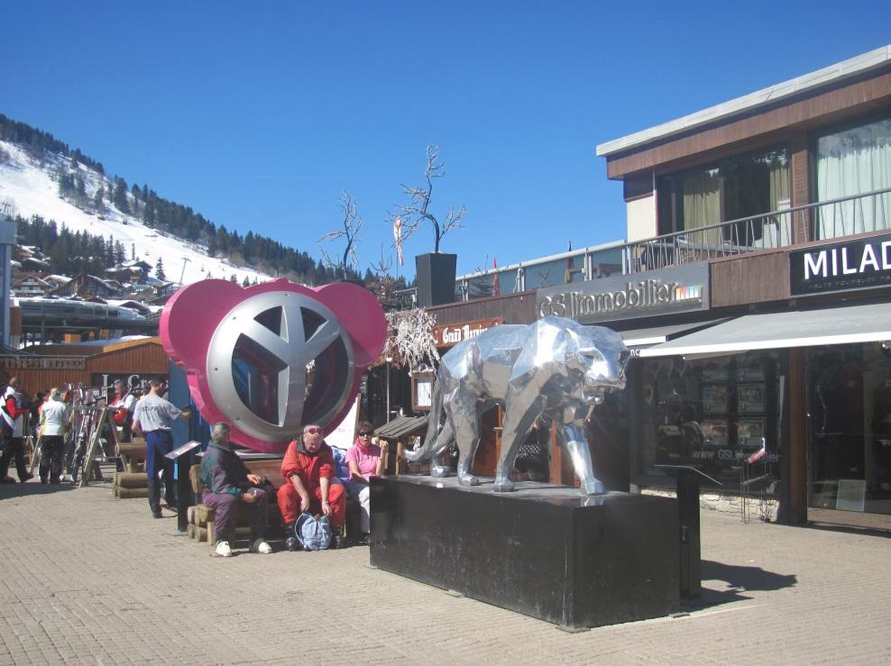 8. Aire de pique-nique improvisée entre deux sculptures d'art contemporain et devant une boutique de fourrure et une agence immobilière haut de gamme à Courchevel 1850 (Piquerey, 2013)