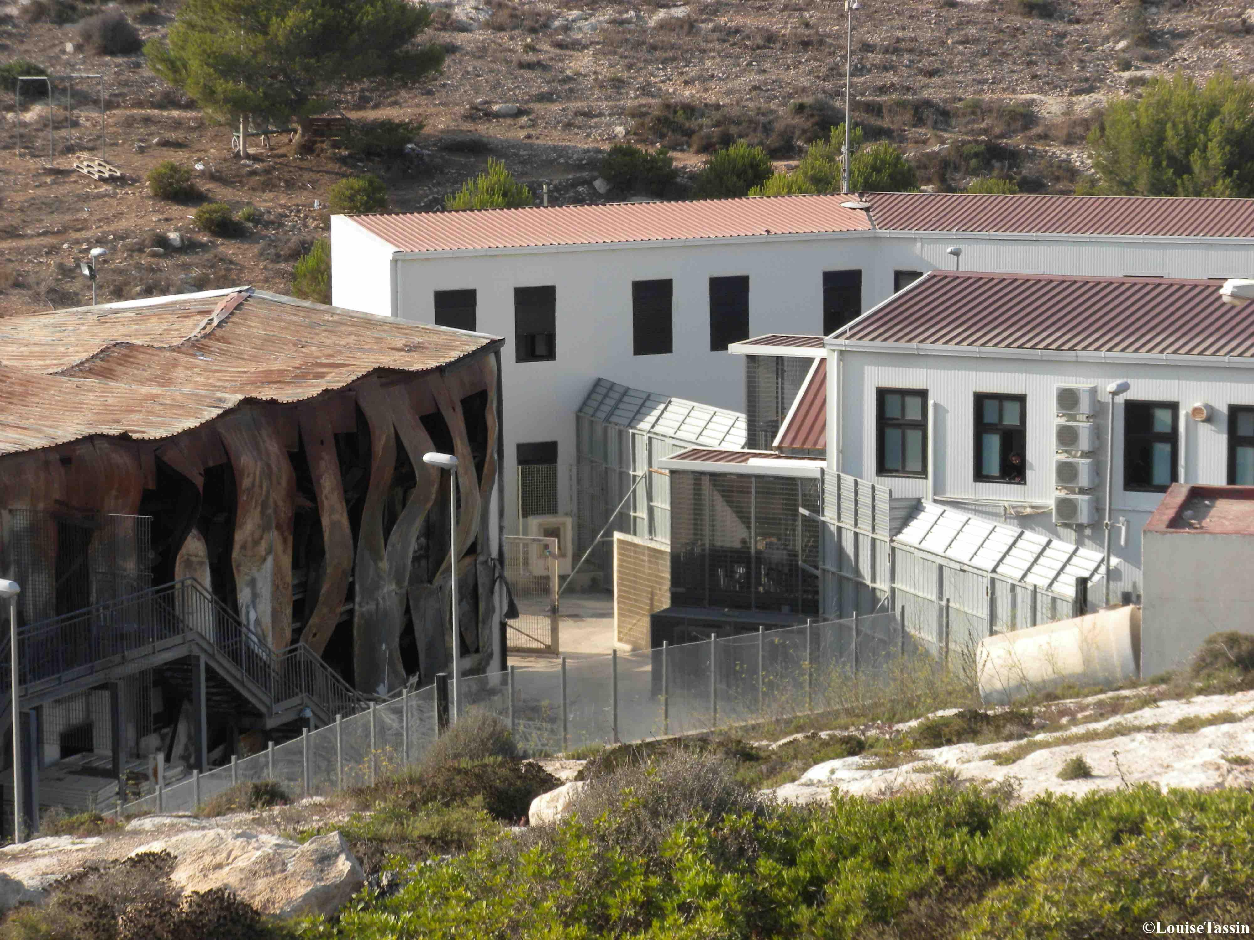 4. Le «centre de premier secours et d'accueil» de Lampedusa en juillet 2013 avec, sur la gauche, les ruines d'un bâtiment brûlé lors d'une révolte (Louise Tassin)