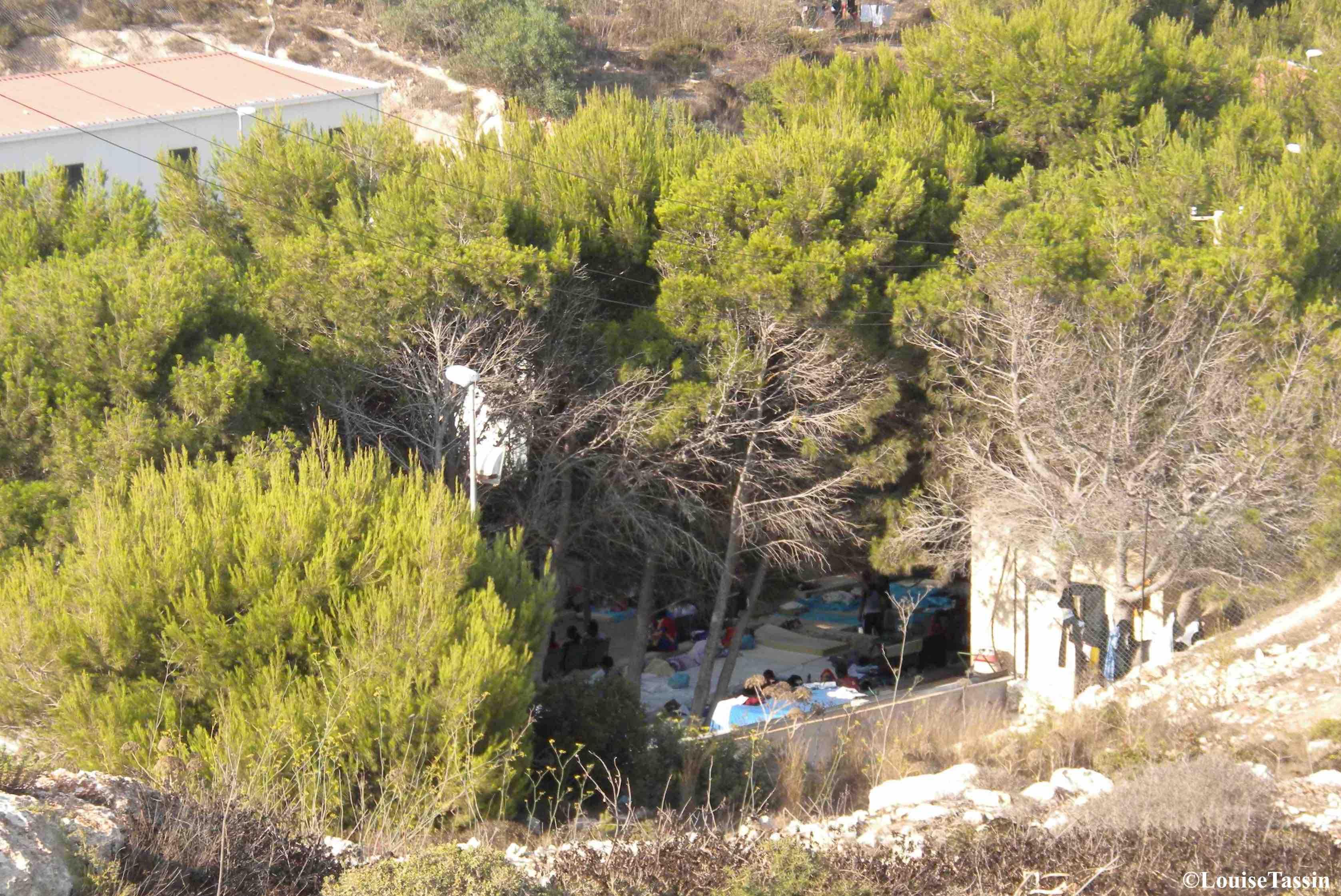 9. Des personnes sont contraintes de dormir à même le sol en extérieur dans le centre de Lampedusa, en juillet 2013 (Louise Tassin)