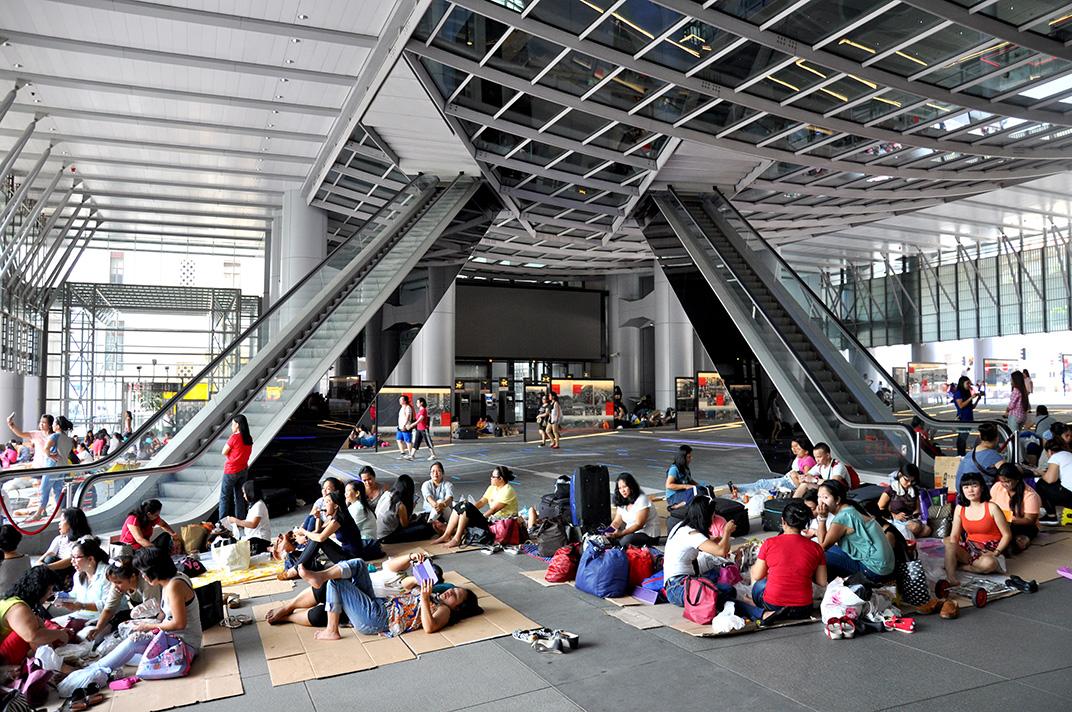 Atrium de la tour HSBC sur Queen's Road un dimanche. Les travailleurs domestiques s'installent sur un espace clairement délimité depuis le réaménagement de l'espace public pour rénovation à la suite du mouvement «Occupy».