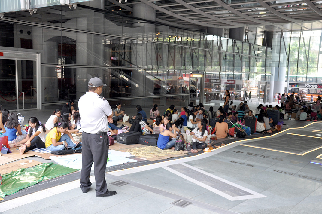 Atrium de la tour HSBC sur Queen's Road un dimanche. Les travailleurs domestiques s'installent sur un espace clairement délimité et surveillé par des gardes de sécurité payés par HSBC qui eux-aussi sont originaires des Philippines.